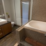 Japanese Tub Brown Tiles Tub And Walls Wooden Bathroom Cabinets Dark Countertop White Wall Medium Toned Wooden Floors Glass Divider