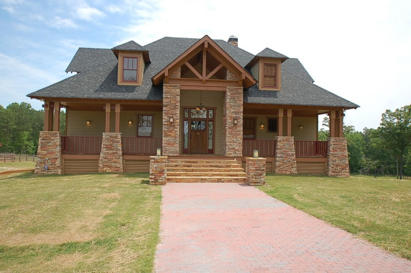 Mission Style home exterior idea with red bricks gate and pillars' base hardwood framed exterior windows and front door dark terracotta roofs beige wood siding exterior walls