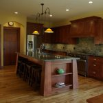 Mission Style Kitchen With Slanted Island Posts Stools Dark Green Countertop Dark Wood Cabinets Dark Wood Island With Open Shelves Medium Toned Wood Floors