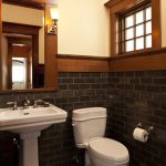 Mission Style Powder Room With White Pedestal Sink White Toilet Black Subway Ceramic Tiles Dark Wood Trims For Window Wood Framed Mirror Light Beige Walls
