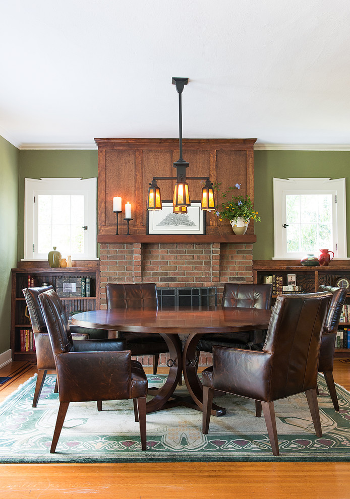 Mission dining room design dark leather dining chairs rounded dining table in dark wood tone wall integrated book racks medium toned wood floors green walls