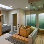 Trendy Bathroom With A Japanese Tub, A Vessel Sink And Pebble Tile Floors Cream Brick Walls Glass Divider Wooden Deck Floor Wooden Floating Cabinets