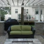 back yard patio designs pergola rattan couch white railing covers stone pavers stairs walls windows