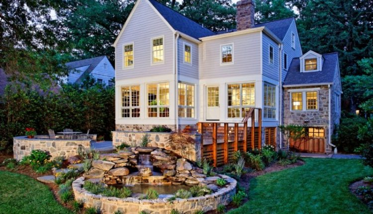 back yard pond grass flowers windows chairs table stones traditional house exterior