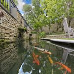 back yard pond koi fish rocking chairs stone wall railing outdoor area traditional landscape