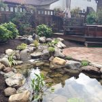 back yard pond stones seating table fence plants flowers traditional landscape