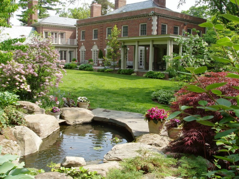 back yard pond flowers stones house grass pillars windows traditional landscape