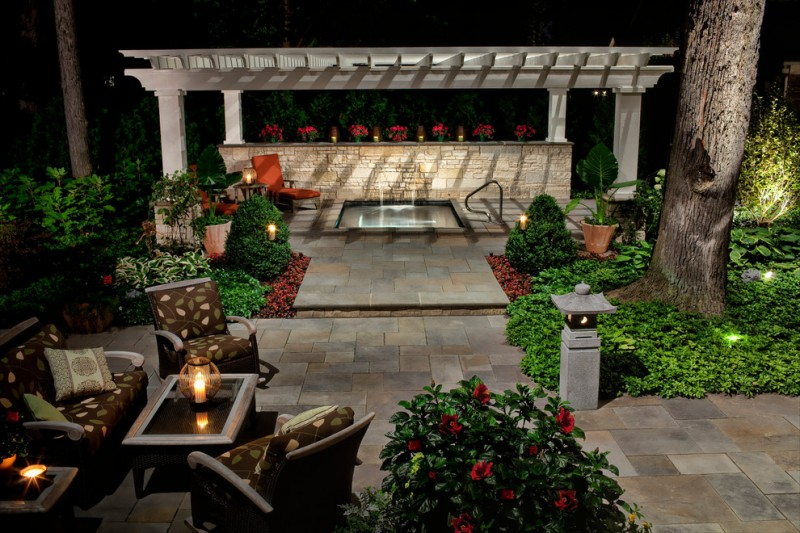backyard patio deigns chairs table pillows beautiful lighting lamps tree plants flowers pergola traditional outdoor area
