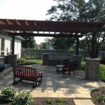 backyard patio designs barbecue grill chairs table pillars pergola tree grass fence plants outdoor area