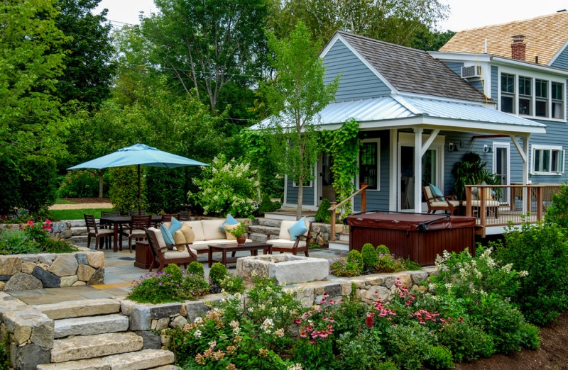 backyard patio designs chairs table sunbrella flowers plants trees railing windows farmhouse outdoor area