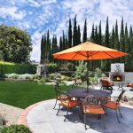 backyard patio designs grass plants chairs table sunbrella fireplace flowers stunning scenery traditional outdoor area