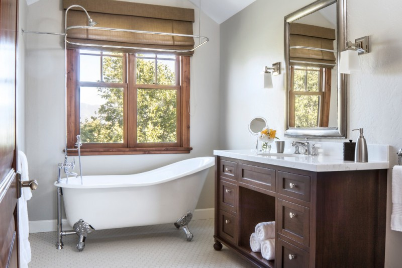 bathroom with Mission Style cabinets silver claw foot bathtub in white metal framed mirror clean white walls wood framed window
