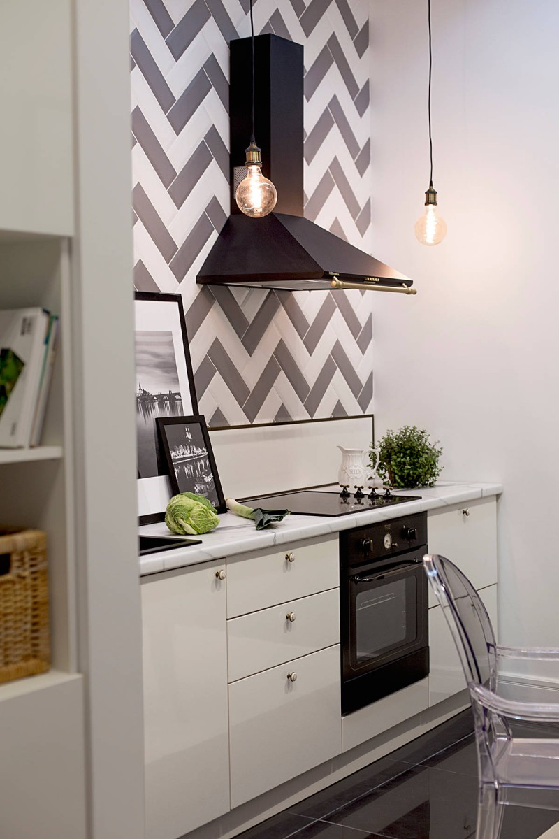 black appliances black hood patterned wall flat panel cabinet white cabinet porcelain floor ceiling lights greenery