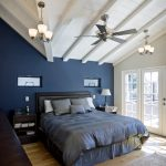 Black Bed Frame With Headboard Navy Blue Walls White Ceilings Light Hardwood Floors Light Toned Area Rug Dark Hardwood Bed Side Tables