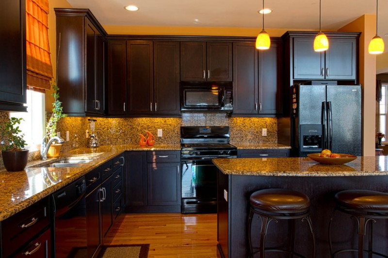 black cabinet black appliances dark bar stool granite countertop granite backsplash pendant lights light wood floor built in sink