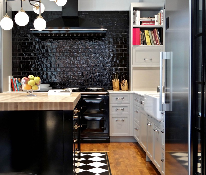 black tiled backplash black appliances black hood black island white cabinet wooden countertop ceiling lamps wooden floor