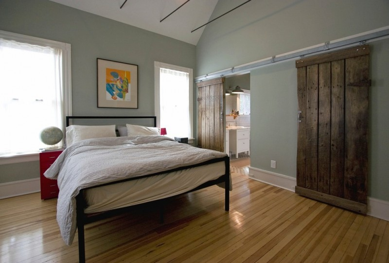 black wrought iron bed frame white bedding treatment honey toned wood floors shabby wood barn doors light gray walls white ceilings red bed side tables