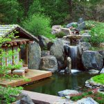 boulder montain rock waterfall pool greenery pink flowers wooden deck rock pathway ottoman chair