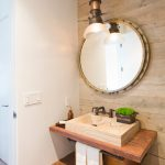 brown wooden vanity pedestal with sandstone sink, dark metal towel lbar under the sink, round mirrors,