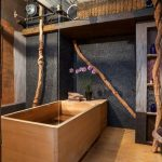 Central Bathroom With Japanese Soaking Tub And Natural Black Pebble Walls Light Toned Cedar Floors A Barn Door Wooden Artworks