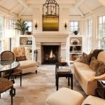 classy sunroom with brown tiles, brown chairs and sofa, fireplace at one side, windows at two side, chandelier