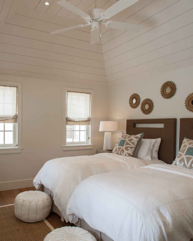 clean white bedding single model bed frames with dark hardwood headboards white walls white wood siding ceilings white ceiling fan medium toned wood floors a pair of white ottoman chairs
