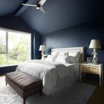 Coastal Bedroom Design With Navy Blue Walls White Bedding Light Wood Bedside Tables Medium Toned Wood Floors Gray Area Rug