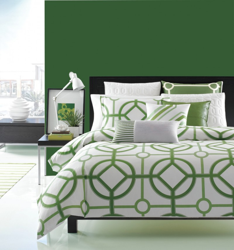 contemporary bedding treatment with various modern patterns in medium and light greens freshly green walls black bed frame with headboard modern bedside table with black top