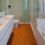 Cork Flooring For Bathroom Herringbone Floor Glass Shower Door And Wall Mirrored Cabinet White Vanity Large Pull Out Drawer Marble Wall