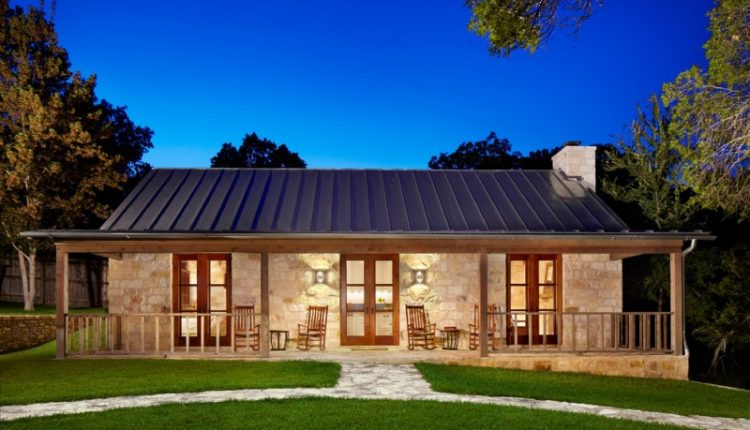 country home exterior with metal roof, light stones wall exterior, wooden frame glass doors, two sets of patio chairs, stones pathways