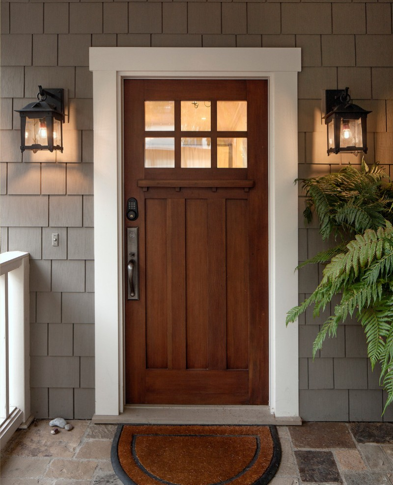 craftsman exterior door a couple of classic exterior lighting fixtures gray subway tiles walls decorative front mat
