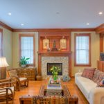 Craftsman Open Concept Living Room Bricks Fireplace With Wooden Mantel A Couple Of Wooden Chair With Puffed Seating Light Beige Couch With Patterned Pillows Wooden Center Table Medium Toned Wood Flo