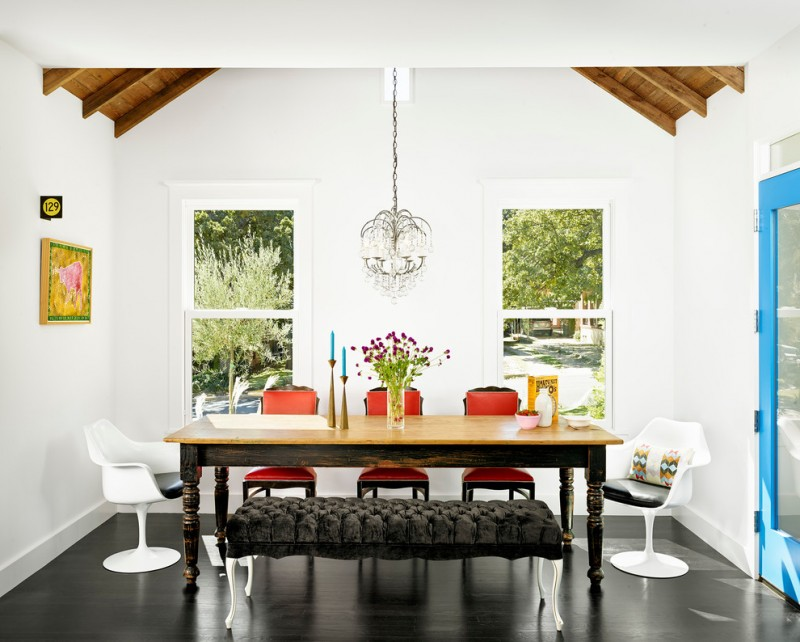 dining room table with bench and chairs dark floor painting flowers windows chandelier contemporary style
