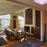 dining room with a collection of rugs, wooden table, chairs, liquor cabinet, fireplace, large windows