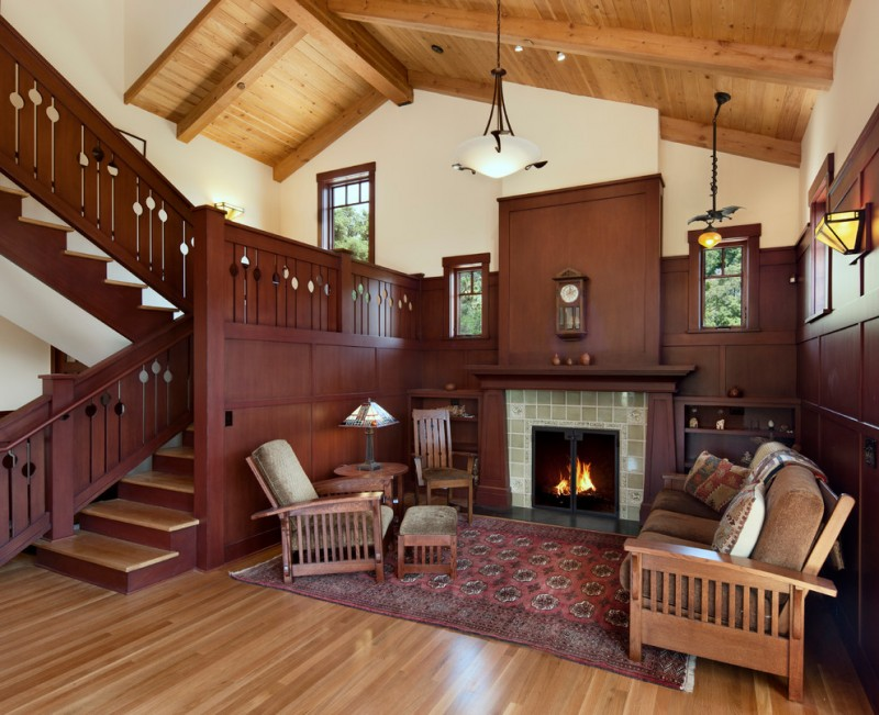 enclosed living room with tiled fireplace dark hardwood wainscoting darkwood stair railing system medium toned wood floors traditional area rug wood living room furniture