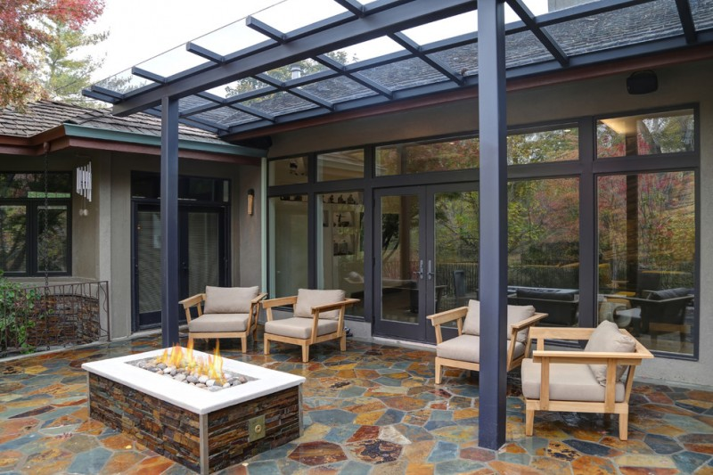 expensive and luxurious backyard patio with dark toned pergola covered with transparent glass panels wooden chairs with white puff comforters center fire pit table slate floors