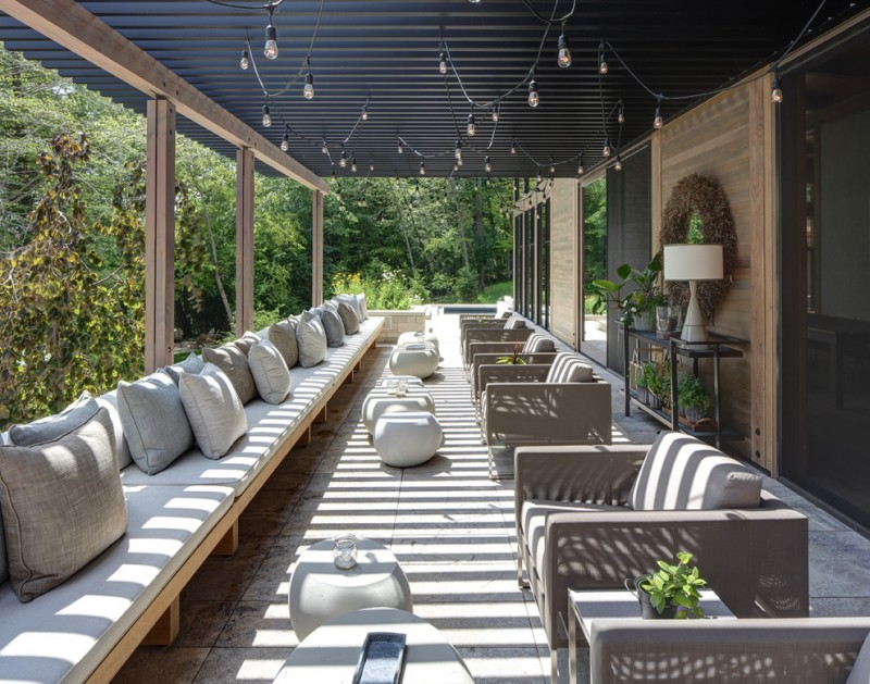 extra large patio with black painted pergola and dangled hang lighting fixtures full length couches with accent pillows rounded center tables in white
