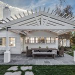 Farmhouse Patio Idea With White Finished Wood Pergola Wood Made Furniture For Patio Stone Paving Floors