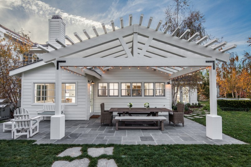 farmhouse patio idea with white finished wood pergola wood made furniture for patio stone paving floors