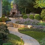 flagstone pathway grass trees outdoor dining space barbeque space stone fireplace garden flowers