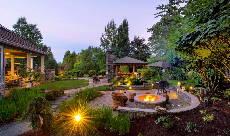 flagstone walkway greenery circular fire pit rattan sitting space gazebo outdoor space stone fireplace