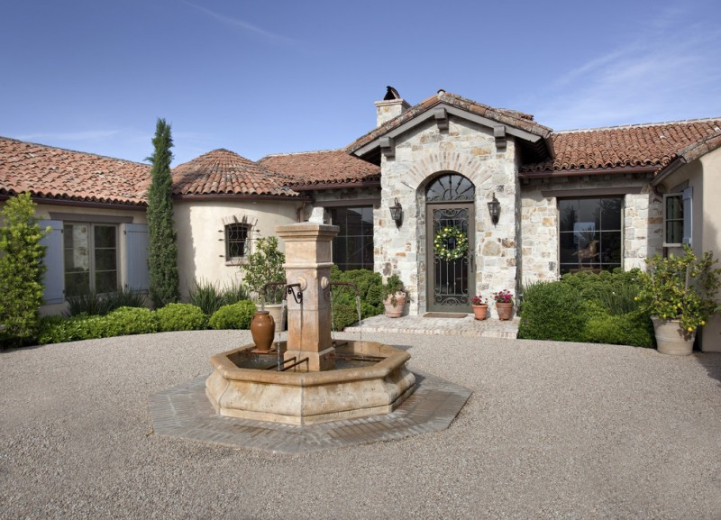front yard fountains sconces stone walls pavers pond windows metal door chimney urn mediterranean design