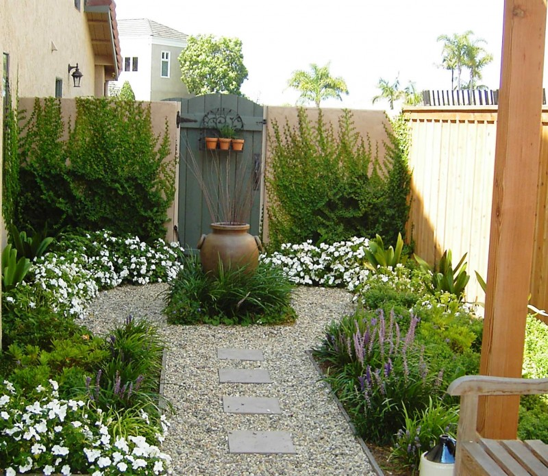 garden urn white flowers stone walkway wooden bench wooden wall wooden door climbing plants purple flowers