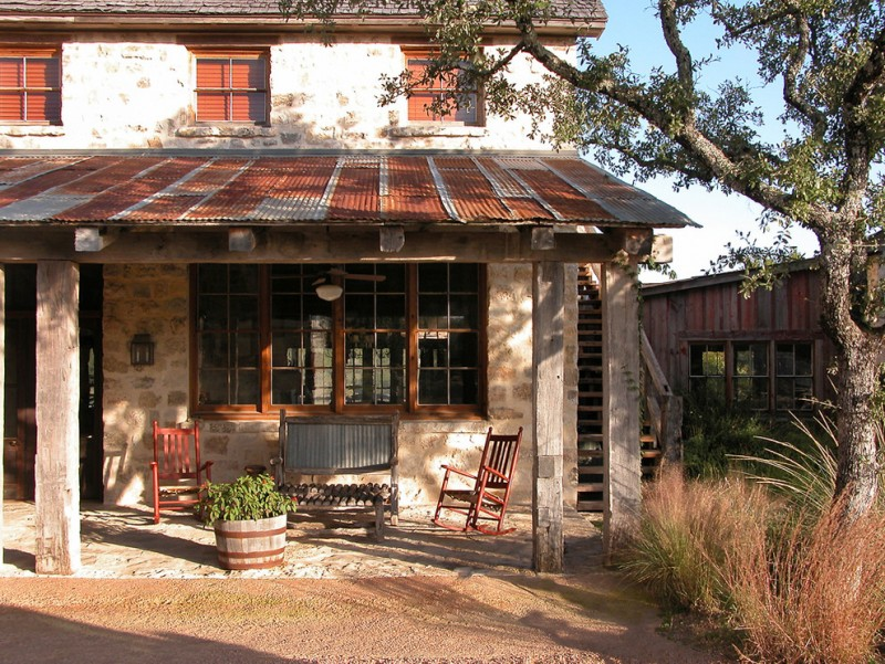 hill country home with old tin roof, stones on the wall and floor, wooden chairs and bench