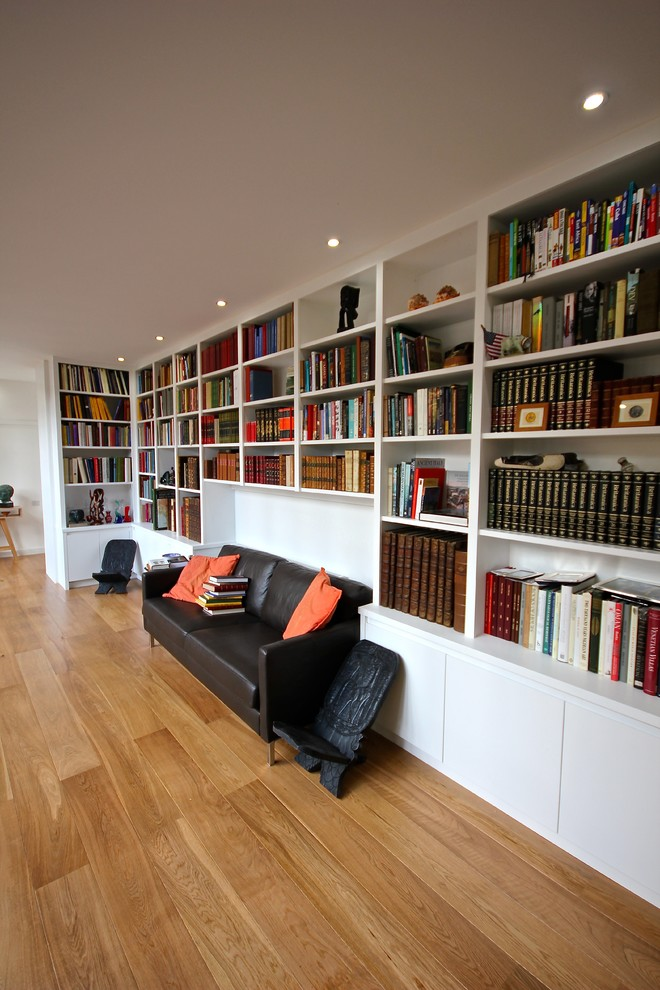 home library shelving large amount bookcase wide bookshelf wood flooring ceiling lights comfortable seating