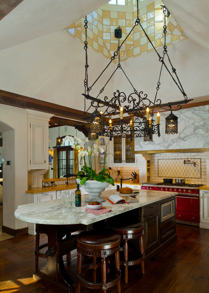 kitchen island with seating for 4 marble countertops stools coloured appliances sink hardwood floors white cabinet chandelier subway tile backsplash mediterranean design
