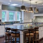 kitchen island with seating for 4 soapstone countertops green backsplash white cabinets chairs hardwood floors pendants farmhouse sink stainless steel appliances transitional design