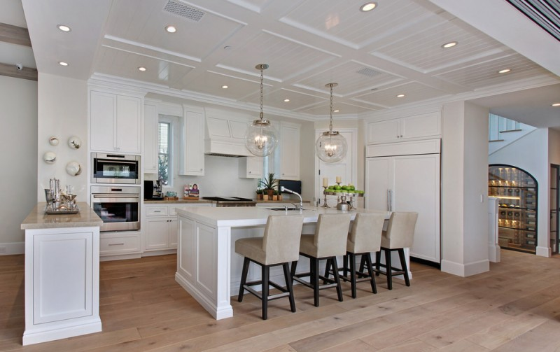 kitchen island with seating for 4 white countertops paneled appliances shaker cabinets ceiling lights pendants chairs backsplash hardwood floors beach style