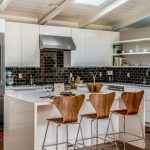 Kitchen With White Sleek Island, Wooden Stool, Black Tiles Backsplash, White Sleek Cabinet And Shelves