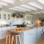 large kitchen islands with seating and storage stools cabinets drawers chopping board shelf flowers clock farmhouse room